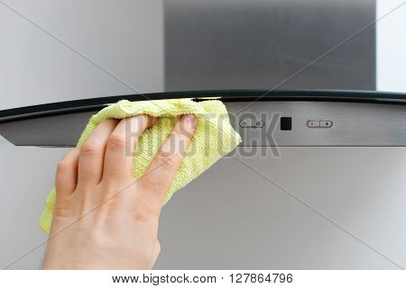Man's hand wipes dust from exhaust hood.