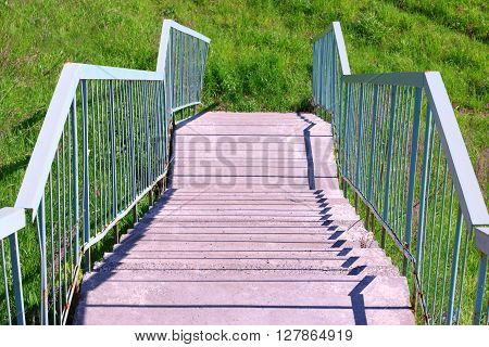 Concrete steps metal blue railing and green grass at summer day