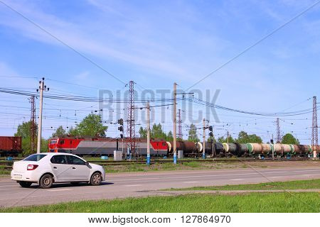 Freight train on railway and car moves on road near green grass at sunny day