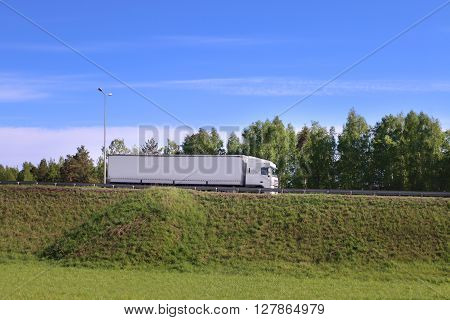 Large white truck moves on road on hill in green grass at sunny day