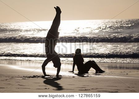 Silhouette of happy couple having fun on beach, man doing headstand.