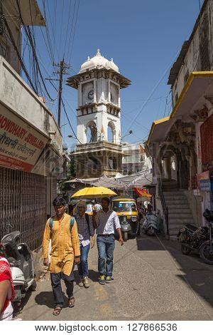 UDAIPUR INDIA - 20TH MARCH 2016: Ghanta Ghar Clock Tower in central Udaipur during the day. People can be seen along the street.