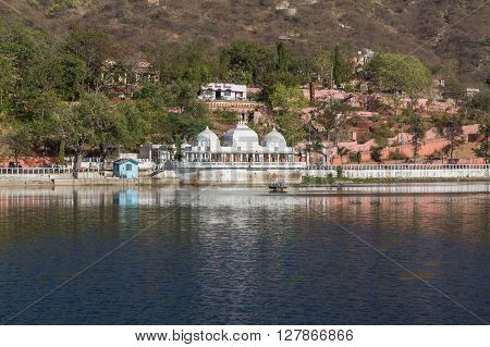 UDAIPUR INDIA - 20TH MARCH 2016: A view of the Doodh Talai Lake in Udaipur during the day. Part of the architecture and people at the waterfront can be seen.