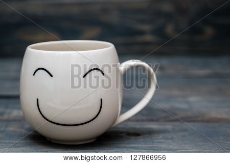 White Cup With Smiley Face On Blue Wooden Table