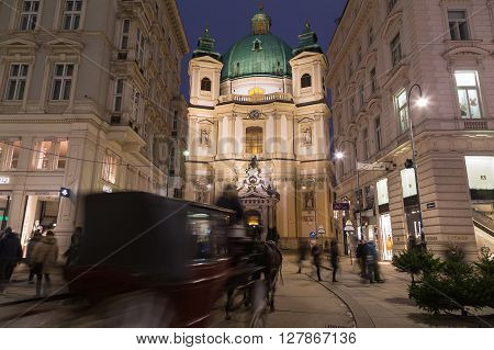 VIENNA AUSTRIA - 20TH DECEMBER 2015: Catholic Church of St. Peter at Night. A horse and chariot and people can be seen.
