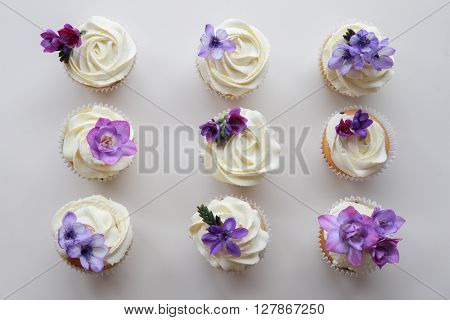 Homemade purple freesia flowers on vanilla cupcakes with whipped cream frosting
