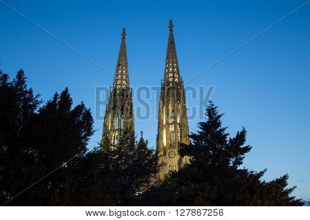Low angle view of the towers on the Votive Church in Vienna at dusk
