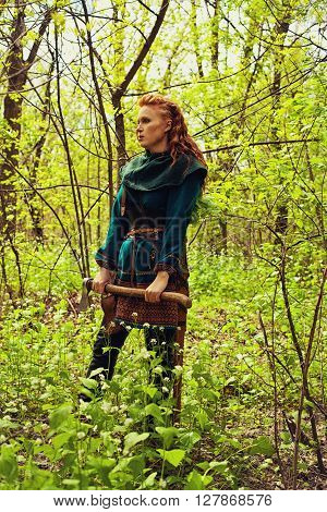 Scandinavian redhead woman standing with axe in a forest