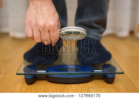 Men is watching his weight over the magnifying glass on scales