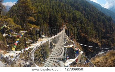 Suspension bridge near village of Namche Bazaar between two mountains, on the abyss of river valley, buddhist flags praying for climbers and trekkers, trekking path, trek to Everest, Sagarmatha, Nepal