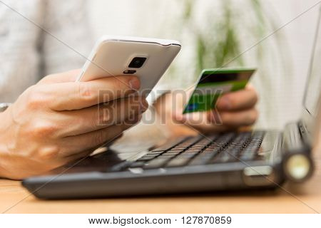 young man is using credit card for online shopping on smart phone and laptop computer