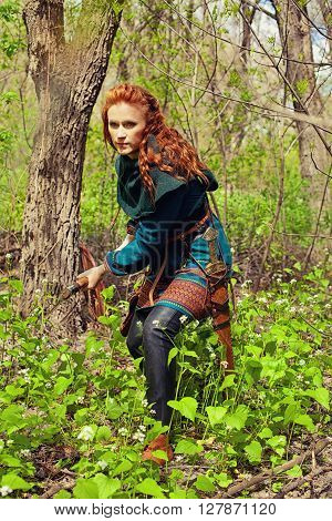 Redhead brave scandinavian woman with axe posing in a forest