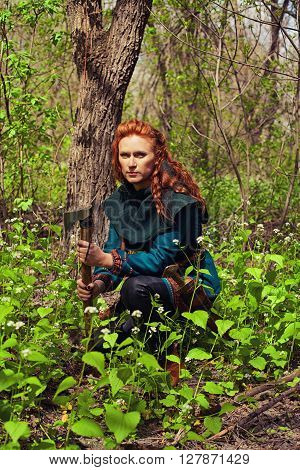 Scandinavian redhead serious maiden sitting in a forest with axe