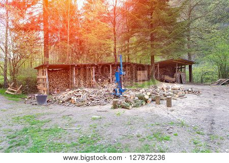 Log splitter in the middle of a rural scene with wood and forests in the background.