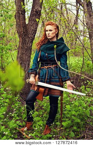 Redhead scandibavian woman posing with sword in a forest
