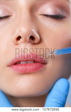 Cosmetic injection on the pretty woman face. Isolated on gray background.