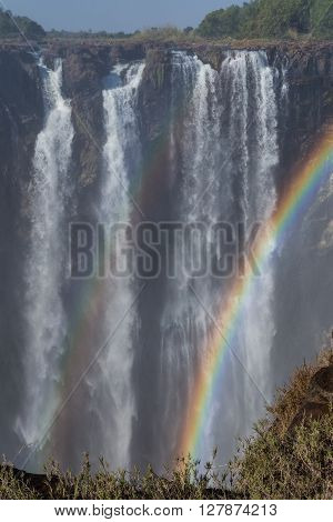 Victoria Falls in October with rainbow crossing. Waterfall running at low speed.