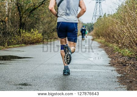 male runner running on asphalt road in puddles