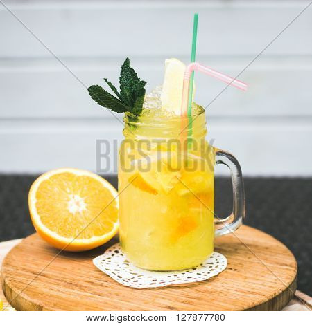 Preparation Of The Lemonade Drink With Tubes. Lemonade In The Jug With Lemons With Mint On The Table