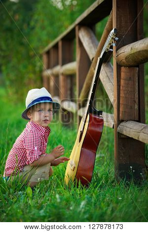 photo of cute little cowboy playing guitar