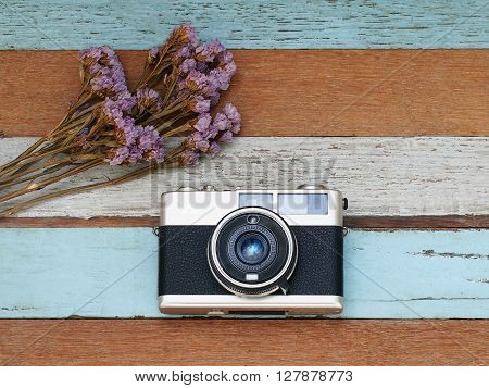 Vintage old camera with flower on the old wooden