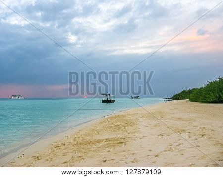 Maldives background. Sunset over the tropical sea and coral beach with colorful cloudy sky. Boats on the horizon. North Male Atoll Asdu, Indian Ocean.