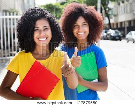 Two latin female students showing thumb outdoor in the city ** Note: Soft Focus at 100%, best at smaller sizes
