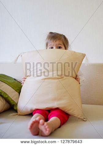 photo of little cute girl hiding behind pillow