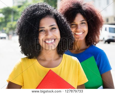 Two latin female students looking at camera outdoor in the city ** Note: Soft Focus at 100%, best at smaller sizes