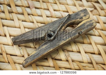 Decrepit wooden clothespin lying on straw mat
