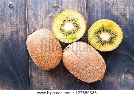Green ripe kiwi fruit on shabby wooden background