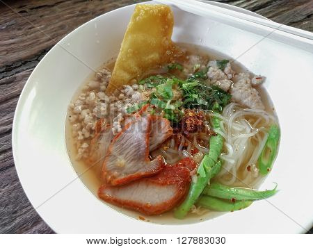 Traditional Thai food Thai style tom yum noodle on wooden table.
