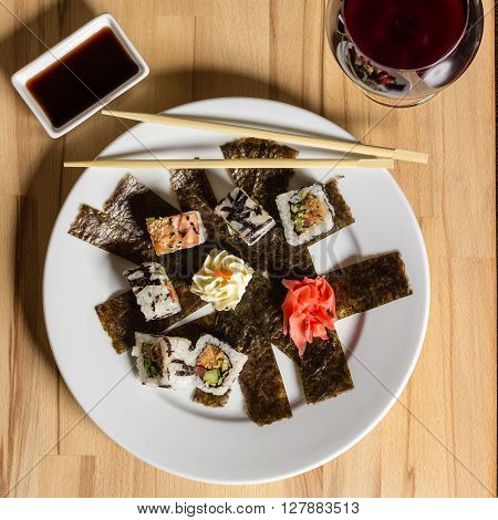 Sushi roll made dish. Sushi assorti on white plate with chopsticks glass of wine. Evening date food photography