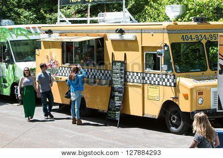 ATLANTA, GA - APRIL 2016: Food trucks lined up in Grant Park serve customers at the Food-o-rama festival in Atlanta GA on April 16 2016 .