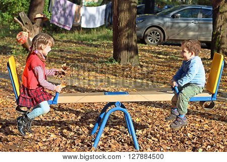 Girl in red vest and her brother ride on seesaw at sunny fall day on playground