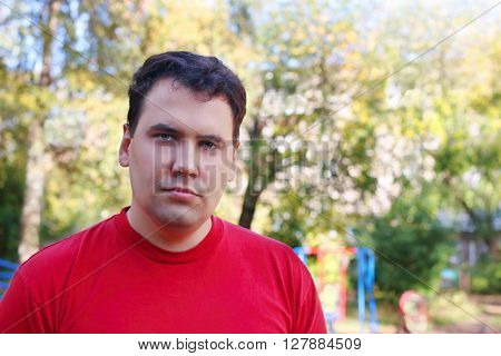 Young handsome man in red stands on children playground at sunny day shallow dof