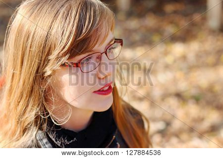 Young smiling woman in glasses looks away at sunny day shallow dof