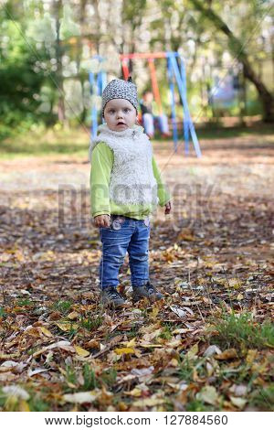 Little cute girl in jeans stands on playground at sunny fall day