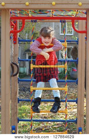 Little girl cheerfully smiles on ladder playground in sunny autumn day