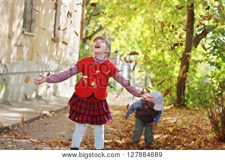 Little girl in red vest throws up leaves in autumn day boy out of focus