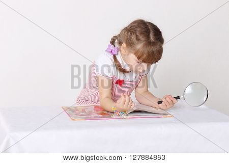 Little cute girl sits oat table reads book and holds magnifying glass in studio