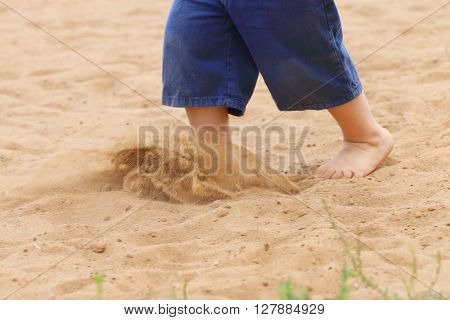 Legs of barefoot of little boy in shorts running on sand close up