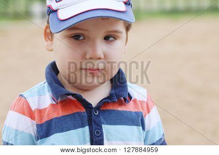 Closeup of little handsome boy in cap outdoor at summer shallow dof