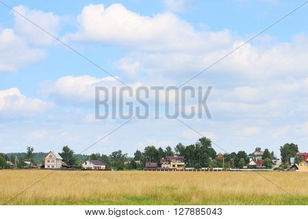 Field with dry grass and houses of village far away at summer sunny day
