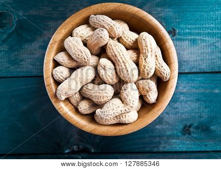 Bowl of fried peanuts with nutshell on turquoise wooden background
