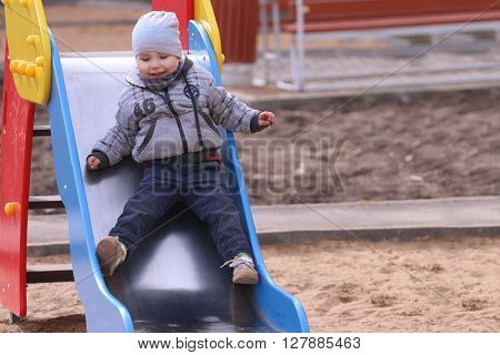 Handsome little boy in grey rides in slide and smiles on playground at spring day