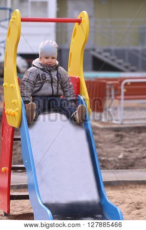 Handsome little boy in grey sits in slide and smile on playground at spring day