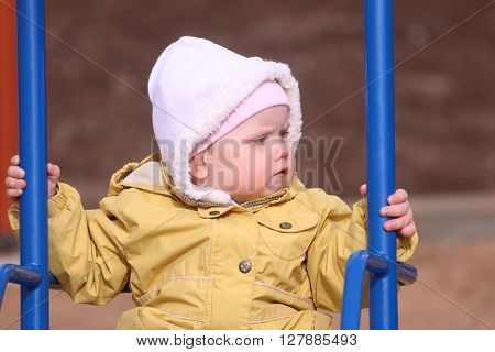 Little cute girl in yellow jacket swings on playground at sunny spring day