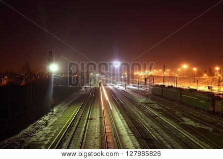 Freight trains with carriages move on railways at snowy winter night long exposure