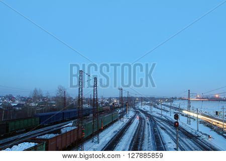 Freight trains with carriages stand on railways at snowy winter evening